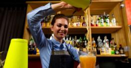 barkeeper Frau macht Entertainment mit Cocktail und Cocktailmixer bei der Landesmeisterschaft