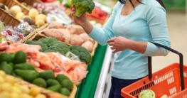 Bewusster einkaufen bei Lebensmittel - Frau befindet sich im Supermarkt in der Gemüseabteilung und hält einen Broccoli