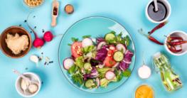 Gesunde Küche mit Salat, Gemüse wie Radieschen, Gurken, Tomaten auf dem Küchentisch