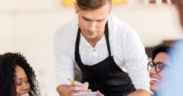 Kellner nimmt die Bestellung von den Gästen am Tisch auf - Kellnerzubehör jetzt auf Gastronomie-MV.de kaufen