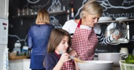 Kleines Mädchen kocht mit der Mutter am Herd gemeinsam bei einem Kochkurs - Kochbücher auf Gastronomie-MV.de für Kochkurse