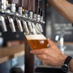 Barchef steht an der Zapfanlage im Restaurant und zapft ein Bier - Passende Biergläser auf Gastronomie-MV.de
